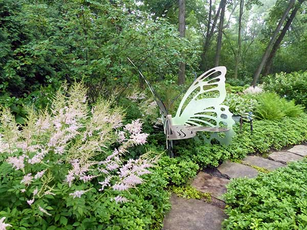 butterfly garden sculpture with pink astilbe