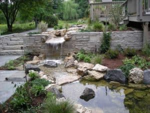 The colors of the bluestone pavers and stone wall are echoed in the pond's boulders and gravel.
