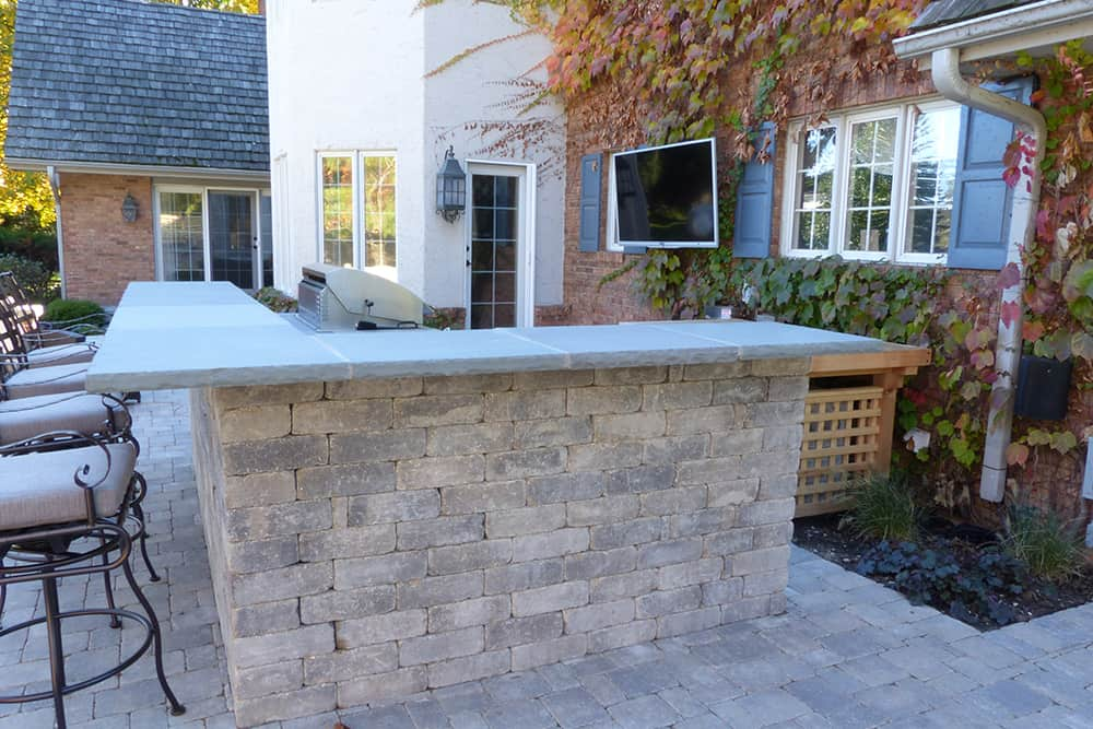 An outdoor bar becomes the center of activity. Made of the same tumbled concrete used for the new patio, and featuring a bluestone top, the bar integrates a built-in grill as well as preparation and serving areas.